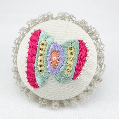Round brooch of embroidery and lace